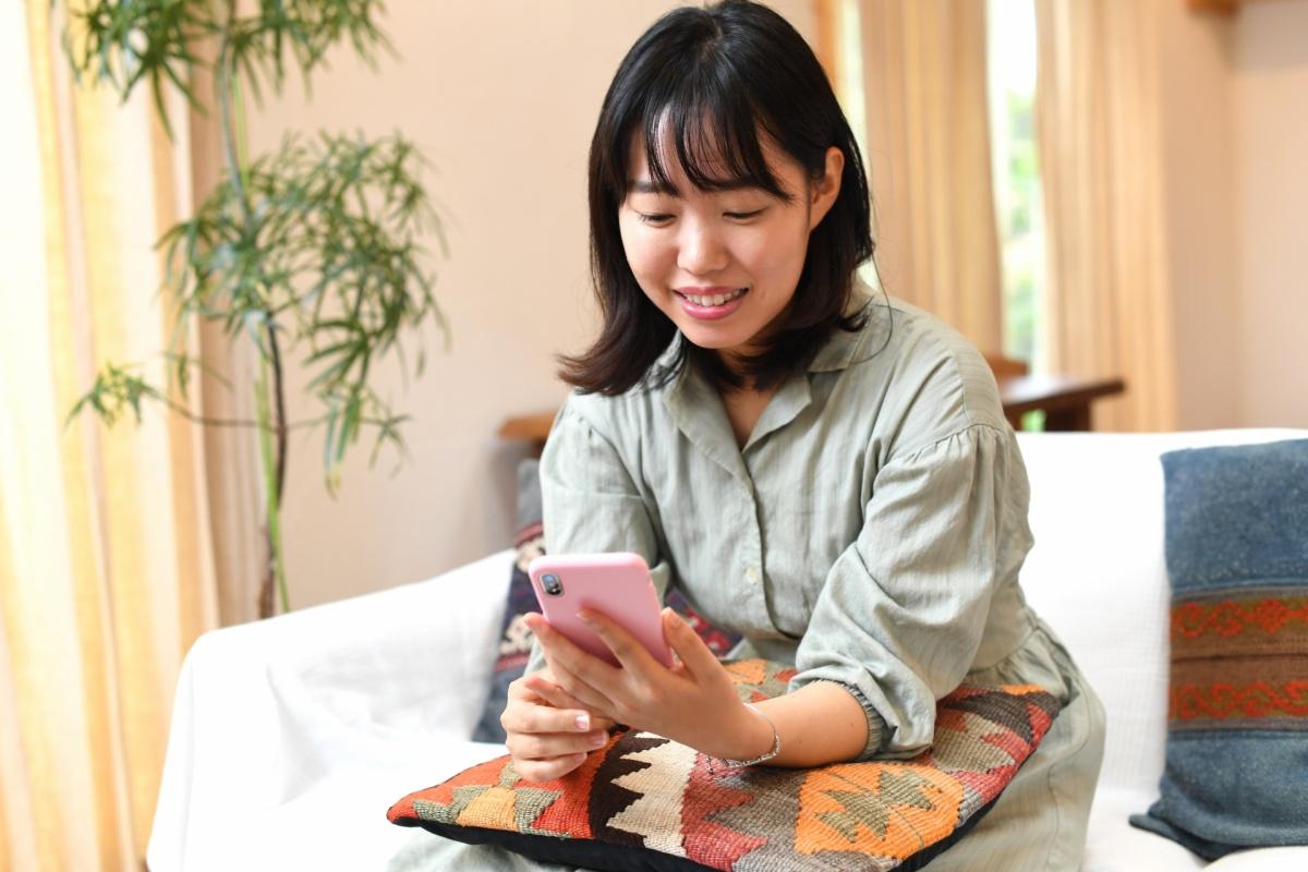 30代前半の独身女性がスマホで婚活アプリをしている